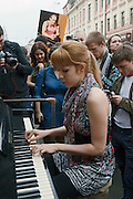 Moscow, Russia, 19/05/2012..A woman plays a piano converted into a mobile artwork with a painting of Russian President Vladimir Putin behind as several thousand artists and opposition activists demonstrate against Putin by walking through Moscow transporting their artworks. The protest coincided with Museum Night, when Moscow's museums are open until midnight with special exhibitions and performances.