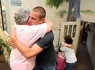 """East Elementary P.E. teacher, Joe Walter gives a goodbye hug to school secretary, Jean Berry, on the last day of school. This is Walter's last day at East Elementary. Walter decided to go back to Ohio to teach, where the pay is better and he will have a gymnasium as a classroom. """"When you can get 10,000 more a year it's tough to pass up,""""  he said."""