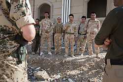 © Licensed to London News Pictures. 09/03/2015. Erbil, Iraq. A Kurdish peshmerga fighters receive feedback from a German army instructor and his translator (left and right), during urban warfare training on at a partially finished housing estate near Erbil, Iraq.<br /> <br /> The training is part of a four week platoon level infantry training package run by coalition forces aimed at improving the efficiency of the Iraqi Security Forces. Photo credit: Matt Cetti-Roberts/LNP