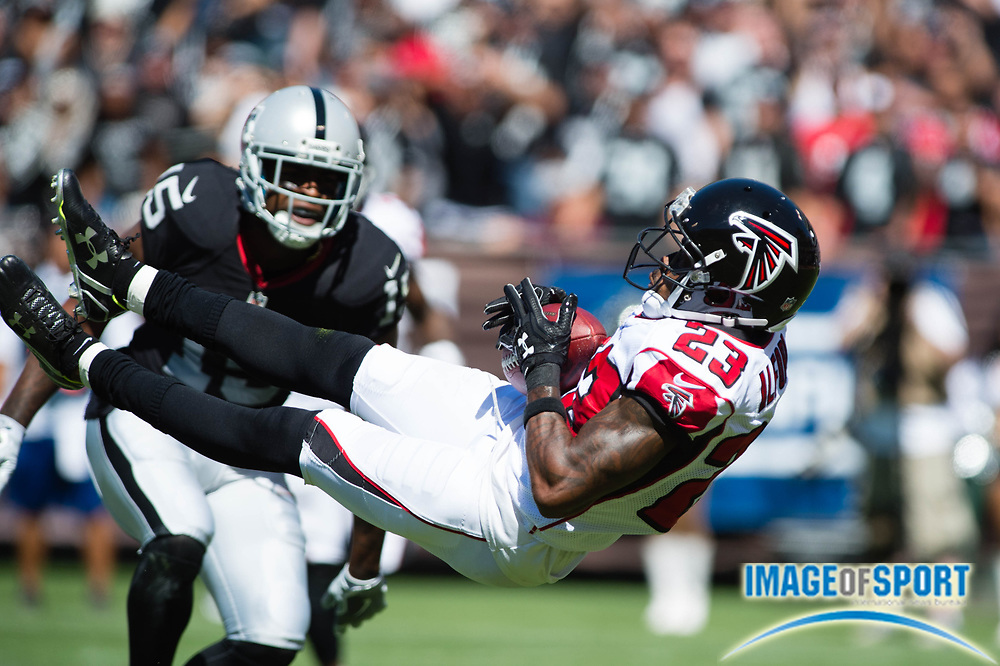 Atlanta Falcons cornerback Robert Alford (23) intercepts a pass intended for Oakland Raiders receiver Michael Crabtree (15) during a NFL game at Oakland-Alameda Coliseum. The Falcons defeated the Raiders 35-28. Photo by Bob Carr