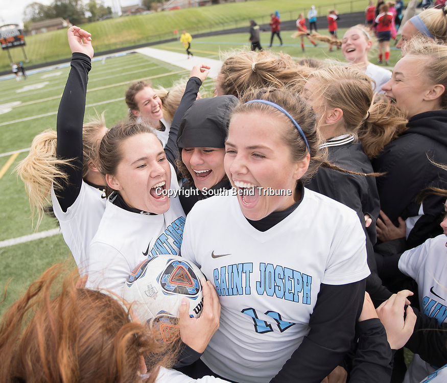 Saint Joseph's Georgia Place, 23, and Natalie Moore celebrate with their team after winning the semi-state soccer game against Belmont at Saint Joseph High School on Saturday, Oct. 20, 2018, in South Bend.