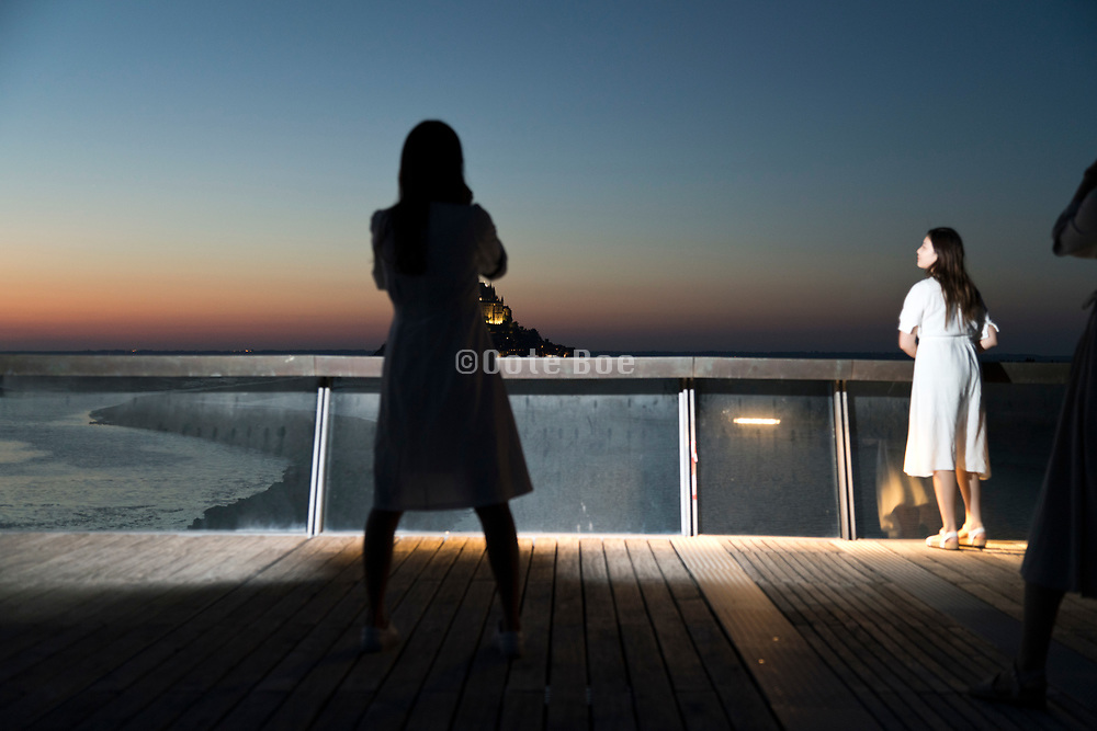 young girls photographing night scene with Mont Saint Michel France Normany.