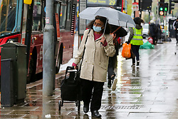© Licensed to London News Pictures. 28/04/2021. London, UK. A shopper wearing a face covering shelters from the rain beneath an umbrella as rain starts to fall in north London for the first time in days.  Photo credit: Dinendra Haria/LNP