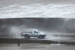 © Licensed to London News Pictures. 27/01/2016. Lyme Regis, UK. A car gets covered in seawater as large waves crash over the Cobb at Lyme Regis harbour in  Dorset, south west England at high tide. The tail end of storm Jonas continues to hit the UK, bringing torrential rain and gales. Photo credit: Peter Macdiarmid/LNP