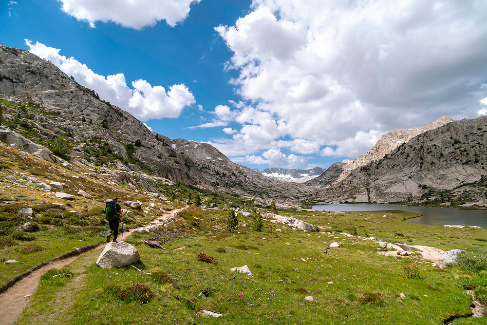 A backpacker passes Evolution Lake. John Muir Trail/Pacific Crest Trail; Sequoia Kings Canyon Wilderness; Kings Canyon National Park; Sierra Nevada Mountains, California, USA.