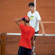 PARIS, FRANCE September 25.  Jannik Sinner of Italy talking with Novak Djokovic of Serbia during a practice match on Court Philippe-Chatrier in preparation for the 2020 French Open Tennis Tournament at Roland Garros on September 25th 2020 in Paris, France. (Photo by Tim Clayton/Corbis via Getty Images)