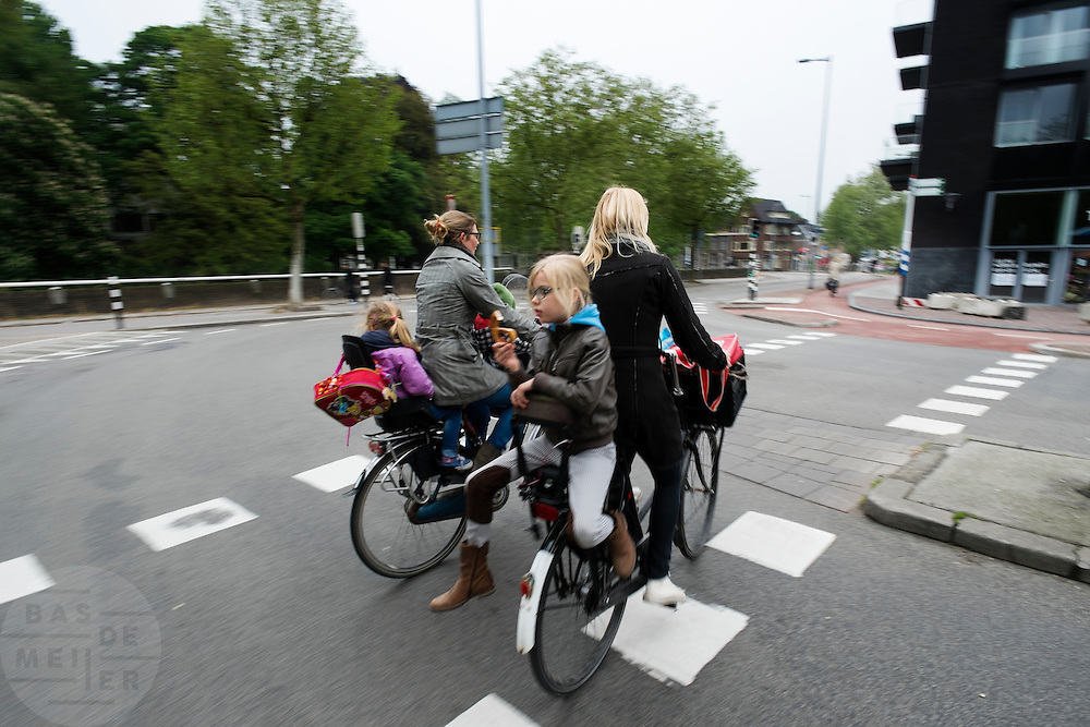Een meisje zit achterstevoren achterop de fiets te eten.<br />