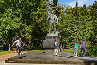 Kiev , Ukraine - August 30, 2019 :  young children practicing skateboard in Mariinsky Park in front of a revolutionary  war memorial statue Landmark of Kiev Ukraine Europe