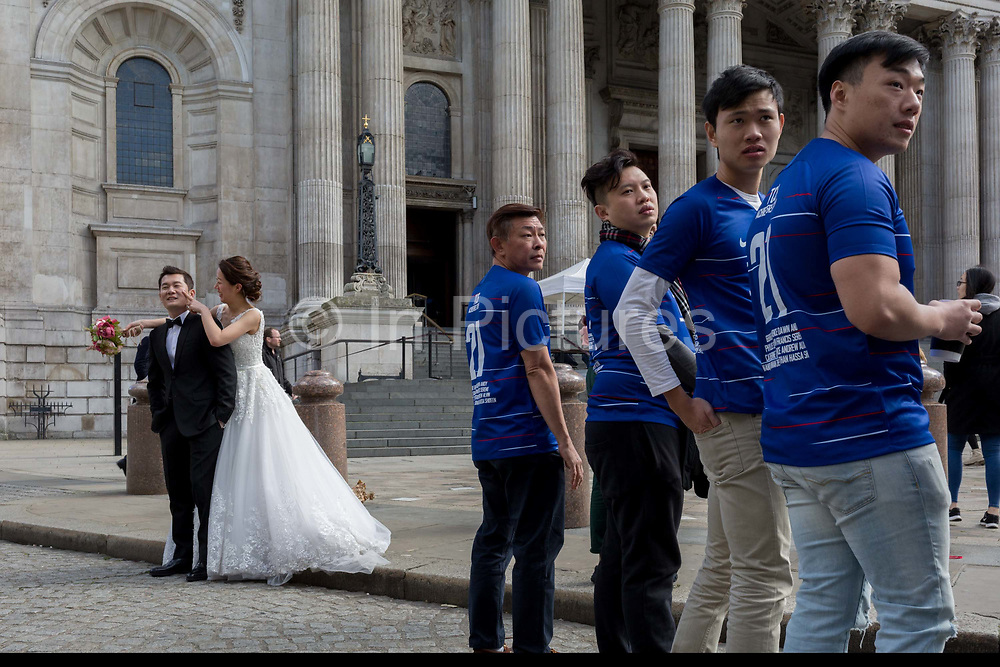 A Chinese wedding couple stand outside St. Pauls Cathedral alongside some Asian corporate achievers, on 25th March 2019, in London, England.