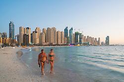 Evening view of beach and skyline of high-rise apartment blocks at JBR Jumeirah Beach Residences in Dubai UAE