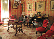 """The Sedman House was built in 1873 in Junction City (1.5 miles north of Nevada City), Montana, USA, for rancher, gold miner and legislator Oscar Sedman. It later became the Junction Hotel, a stable, and finally was moved to Nevada City for preservation. This Victorian era living room is furnished with piano, wood stove, red velvet padded chairs, table, books, pictures hung on wall. Nevada City was a booming placer gold mining camp from 1863-1876, but quickly declined into a virtual ghost town. This fascinating town inspires you to imagination what life must have been like in early Montana when gold was discovered at nearby Alder Gulch. More than 90 buildings from across Montana have been gathered for preservation at Nevada City, mostly owned by the people of the State of Montana, and managed by the Montana Heritage Commission. In 2001, the excellent PBS television series """"Frontier House"""" used one of the buildings and its furnishings to train families in re-creating pioneer life. A miner's court trial and hanging of George Ives in the main street of Nevada City was the catalyst for forming the Vigilantes, a group of citizens famous for taking justice into their own hands in 1863-1864. Directions: go 27 miles southeast of Twin Bridges, Montana on Highway 287."""