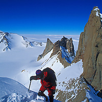 Mountaineer Michael Graber ascends a satellite peak of the Troll's Castle (bkg.) in Queen Maud Land, Antarctica.  Behind is the vast polar plateau.