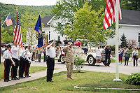 Gilford Police Chief Anthony Bean Burpee and Lt. Col. Kurt Webber (retired) salute and honor veterans at the World War I and II monument during Memorial Day services in Gilford Monday morning.  (Karen Bobotas/for the Laconia Daily Sun)