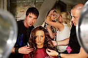 Hairstylists style a model's hair before a runway show in New York, Wednesday, September 7, 2005.