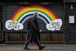 © Licensed to London News Pictures. 07/11/2020. London, UK. A man wearing a face mask walks past a mural painted outside a boarded up restaurant on Old Compton Street in Soho. New restrictions are now in force in England and pubs, restaurants, non-essential shops and gyms have closed. Photo credit: Rob Pinney/LNP