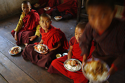 Monks eat breakfast and perform morning chores in a monastery near Trashi Yengtse October 14, 2005. (Ami Vitale)