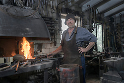 Blacksmith heating iron bar in forge at workshop, Bavaria, Germany