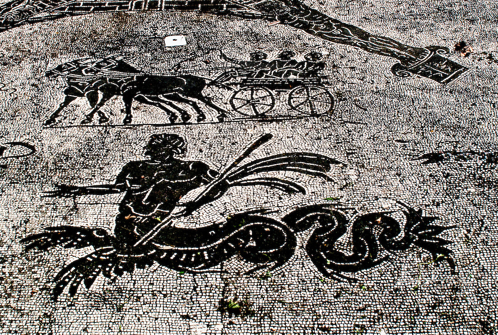 Black and white mosaic floor of the so-called Baths of the Coachmen, Ostia Antica, shows a pair of mules drawing a carriage with 3 passengers, and a human - sea monster creature who wields a long staff.  This facility was a barracks and stopover place for the muleteers who drove the cabs back and forth between Ostia and Rome.
