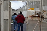 Visitors walking through the secure perimeter gate. HMP Send, closed female prison. Ripley, Surrey.