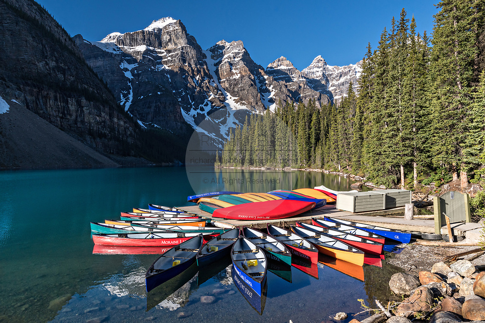 Colorful canoes docked in the turquoise waters of Lake Louise and the snow dusted Fairview Mountain behind in Banff National Park in Alberta, Canada.