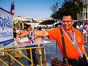 """29 DECEMBER 2013 - BANGKOK, THAILAND: An anti-government protestor makes a donation to support the cause near Democracy Monument in the old part of Bangkok during a protest against the ruling Pheu Thai party. Protest leader and former Deputy Prime Minister Suthep Thaugsuban announced an all-out drive to eradicate the """"Thaksin regime."""" The anti-government protesters have vowed to continue their protests even though the government has been dissolved and new elections called for in February. The protests have been ongoing in Bangkok since November and are growing increasingly violent.              PHOTO BY JACK KURTZ"""