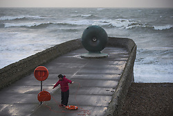 © Licensed to London News Pictures. 27/10/2013. BRIGHTON, UK A man checks a life ring on the seafront. Waves at Brighton seafront this morning as Britain was braced for the worst storm for a decade today, which is set to bring driving rain and winds of up to 90mph to some areas. Photo credit : LNP