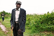 An adult African male stands in a dirt path in Lwala, Kenya.