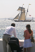 USA, Newport, RI - 2004  - A couple with baby in stroller watch the Tallships 'Parade of Sail' event from Goat Island as square rigged sailing ships from around the world sail past viewers on shore.