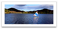 A small sailboat in Mirror Lake at Lake Placid in the Adirondack Mountains of New York State, USA