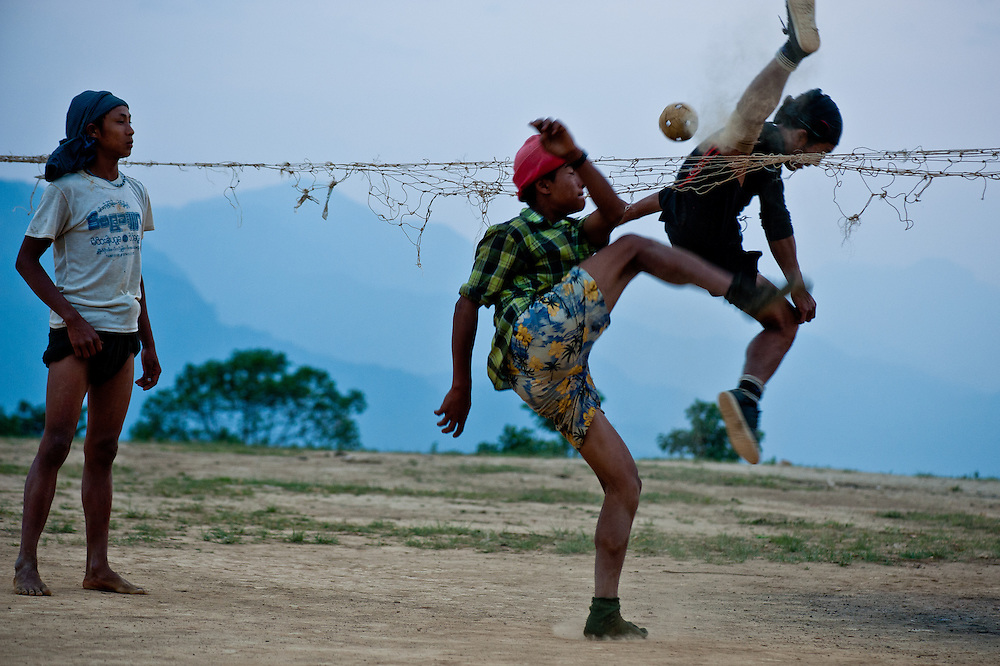 Boys play a cross between soccer and volleyball with a rattan ball on the plateau overlooking the valley below Layshee.
