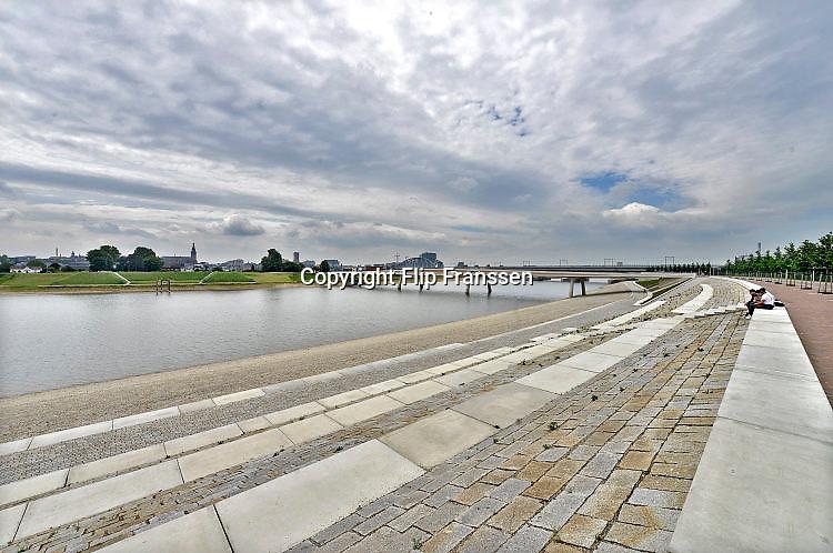 Nederland, Nijmegen, 24-5-2017 De bijna 4 km. lange nevengeul van de Waal bij Lent,is  Spiegelwaal genoemd.  Grootste onderdeel van de vele werken van Rijkswaterstaat om bij hoogwater een betere waterafvoer in de rivier te hebben. Het dorp veurlent is op een kunstmatig eiland komen te liggen met twee kleinere bruggen als ontsluiting. Een voetgangersbrug, de steltlopersbrug voor wandelaars naar het recreatiegebied. Ruimte voor de rivier, water, waal. In de nieuwe dijk wordt een drempel gebouwd die stapsgewijs water doorlaat en bij hoogwater overloopt. Het levert de regio ook een nieuw recreatiegebied op waar in de zomer volop gezwommen kan worden.The Netherlands, Nijmegen Measures taken by Nijmegen to give the river Waal, Rhine, more space to flow during highwater and to prevent the risk of flooding. Room for the river. Reducing the level, waterlevel. Large project to create a new paralel gully, an extra flow of water, so the river can drain more water during highwater. Due to climate change and expected rise, increase of the sealevel, the Dutch continue to protect their land from the water. Foto: Flip Franssen