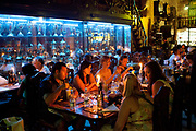 A group of tourists mostly female eat at Los Nardos, one of Havana's most famous restaurants. Trophies and ambiently lit decor in the background.