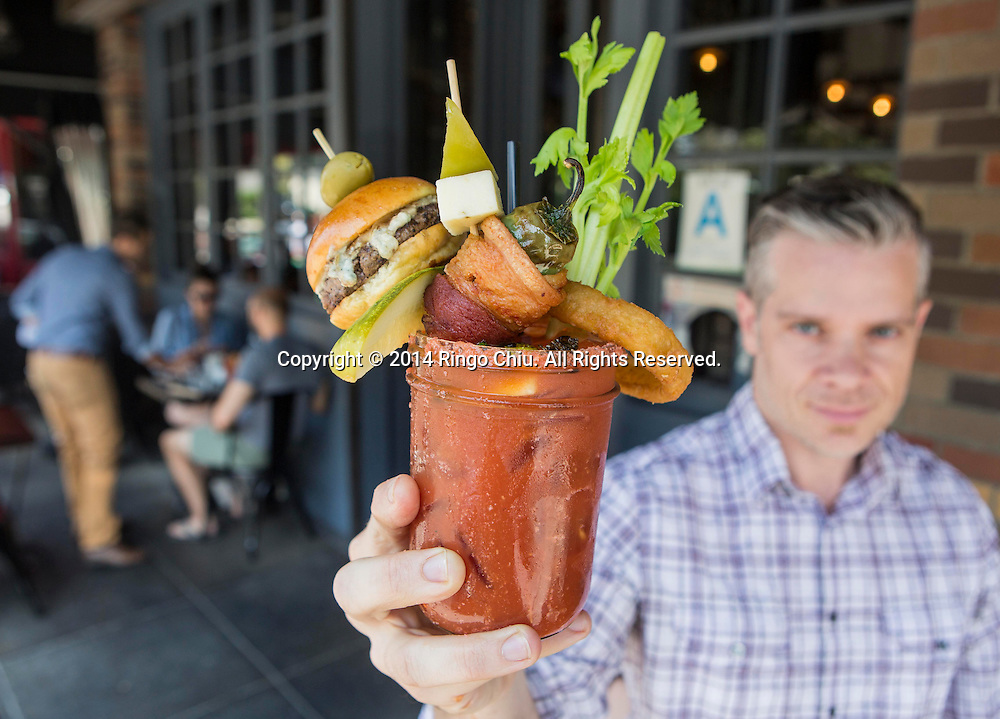 LOS ANGELESE, CA - MAY 25, 2014:   Larry Caldwell shows a glass of  Bloody Mary (the Bloody Royale) at Franklin and Company.  (Photo by Ringo H.W. Chiu / For The Times)(Photo by Ringo Chiu/PHOTOFORMULA.com)