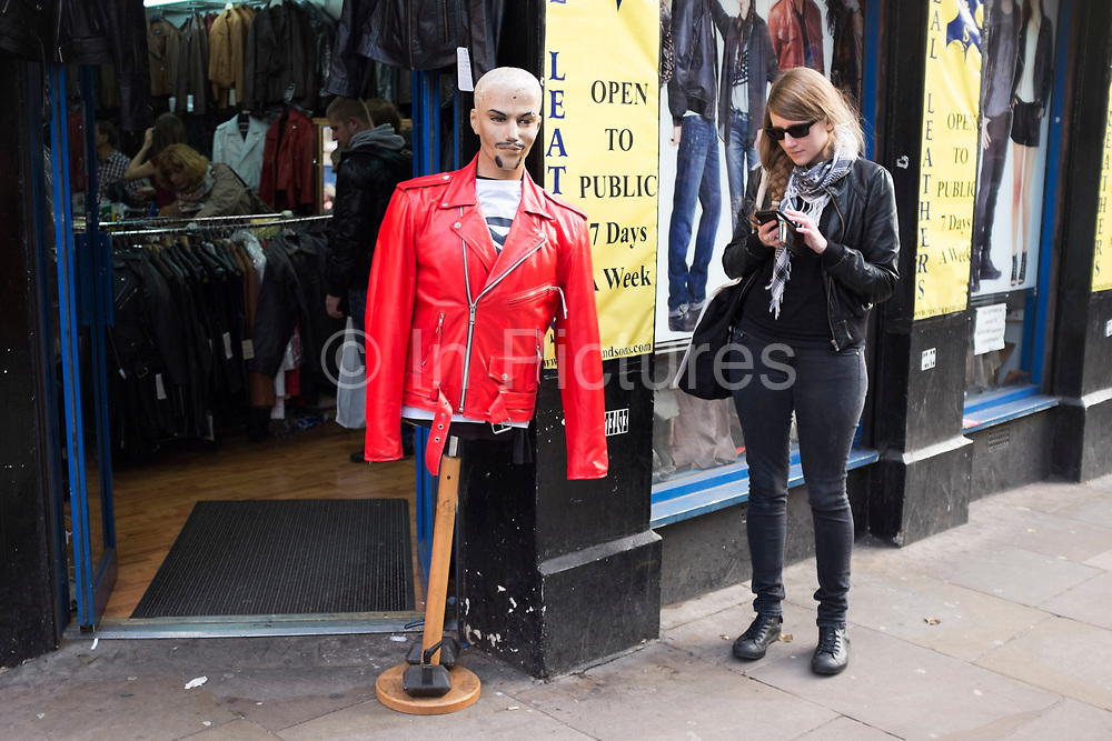 Girl texting while standing next to a mannequin wearing a red leather jacket outside a shop on Brick Lane, London, UK.