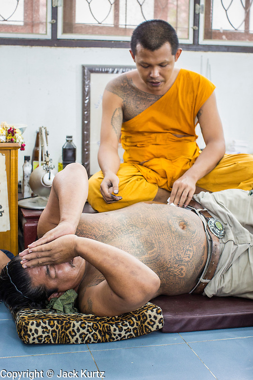 """22 MARCH 2013 - NAKHON CHAI SI, NAKHON PATHOM, THAILAND: A man prays while a monk gives him a sacred Sak Yant tattoo at Wat Bang Phra. Wat Bang Phra is the best known """"Sak Yant"""" tattoo temple in Thailand. It's located in Nakhon Pathom province, about 40 miles from Bangkok. The tattoos are given with hollow stainless steel needles and are thought to possess magical powers of protection. The tattoos, which are given by Buddhist monks, are popular with soldiers, policeman and gangsters, people who generally live in harm's way. The tattoo must be activated to remain powerful and the annual Wai Khru Ceremony (tattoo festival) at the temple draws thousands of devotees who come to the temple to activate or renew the tattoos. People go into trance like states and then assume the personality of their tattoo, so people with tiger tattoos assume the personality of a tiger, people with monkey tattoos take on the personality of a monkey and so on. In recent years the tattoo festival has become popular with tourists who make the trip to Nakorn Pathom province to see a side of """"exotic"""" Thailand. The 2013 tattoo festival was on March 23.    PHOTO BY JACK KURTZ"""