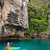 """Climber """"deep water soloing"""" without rope, returning to the sea... Poda Island, Krabi, Thailand"""