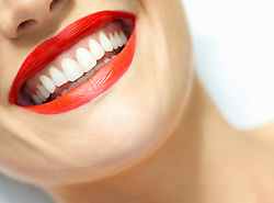 Close up of Woman's Smiling Mouth with Red Lipstick