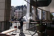 A vaping smoker exhales his vape smoke while standing in late-summer sunshine near Liverpool Street Station in the City of London, the capitals financial district, on 24th September 2021, in London, England.