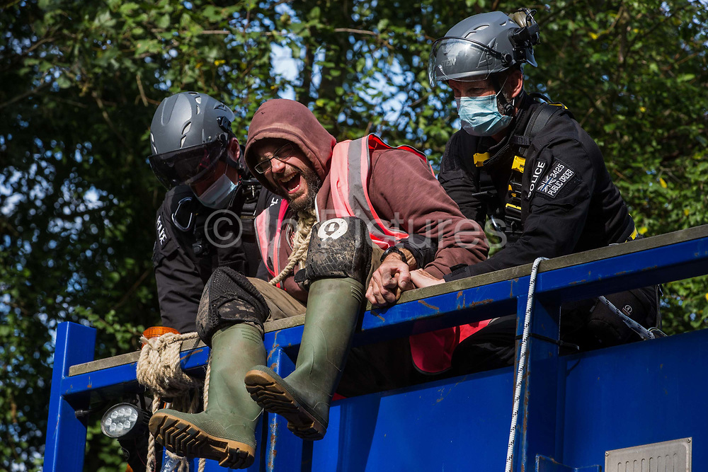 A Thames Valley Police officer uses force to remove the hand of an anti-HS2 activist glued to a HGV with a rope around his neck in order to block its passage to works for the HS2 high-speed rail link on 28 September 2020 in Denham, United Kingdom. Environmental activists continue to try to prevent or delay works on the controversial £106bn project for which the construction phase was announced on 4th September from a series of protection camps based along the route of the line between London and Birmingham.