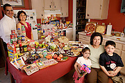 (MODEL RELEASED IMAGE). The Fernandez family in the kitchen of their San Antonio, Texas home with a week's worth of food. Lawrence, and wife Diana, standing, and Diana's mother, Alejandrina Cepeda, sitting with her grandchildren Brian, and Brianna. The Fernandez family is one of the thirty families featured in the book Hungry Planet: What the World Eats (p. 270).