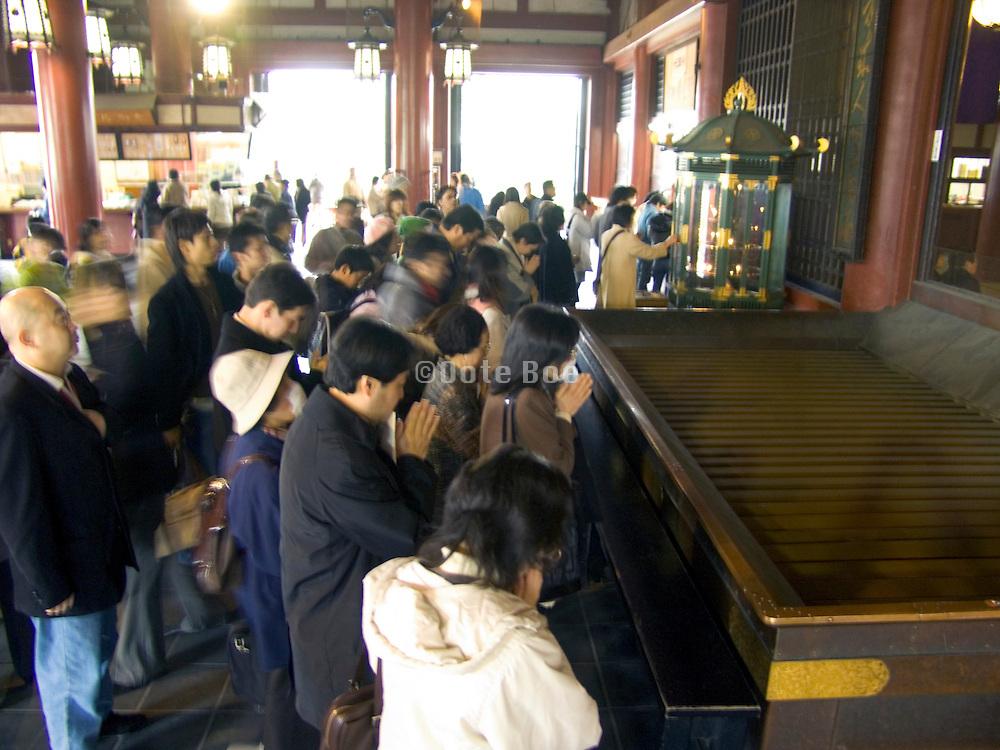 People praying at the Asakusa Kannon Temple Tokyo