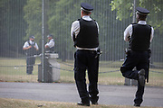 UK Met police officers guard a temporary perimeter fence encircling Winfield House, the official residence of the US Ambassador during the visit to the UK of US President, Donald Trump, on 12th July 2018, in Regents Park, London, England.