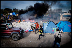 October 27, 2016 - Calais, Northern France, France - Image ©Licensed to i-Images Picture Agency. 27/10/2016. Calais, France. Calais Jungle Migrant Camp. Volunteer firefighters put of fires in the  middle of the burning tent in  the migrant camp as refugees start to leave the Calais Jungle migrant camp the day after it caught fire and the French police closed it down. Picture by Andrew Parsons / i-Images (Credit Image: © Andrew Parsons/i-Images via ZUMA Wire)