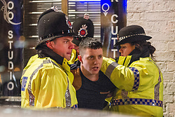"""© Licensed to London News Pictures . 15/12/2012 . Manchester , UK . Police detain a man . Revellers enjoy a wet but busy night out on one of the last weekends before Christmas , a traditionally busy time when office parties and clubbers decent on bars and clubs , often known as """" Mad Friday """" . Photo credit : Joel Goodman/LNP"""