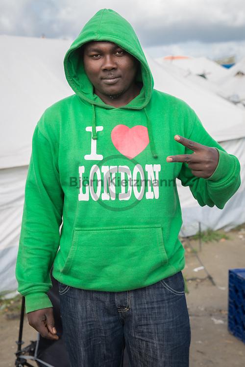 """Calais, Pas-de-Calais, France - 17.10.2016    <br />  <br /> A sudanese refugee with a """"I love London""""-shirt. The man lives since 4 month in the """"Jungle"""" refugee camp on the outskirts of the French city of Calais. Many thousands of migrants and refugees are waiting in some cases for years in the port city in the hope of being able to cross the English Channel to Britain. French authorities announced that they will shortly evict the camp where currently up to up to 10,000 people live.<br /> <br /> Ein sudanesischer Fluechtling mit einem """"I Love London""""-Pullover. Der Mann lebt seit 4 Monaten im """"Jungle"""" Fluechtlingscamp am Rande der franzoesischen Stadt Calais. Viele tausend Migranten und Fluechtlinge harren teilweise seit Jahren in der Hafenstadt aus in der Hoffnung den Aermelkanal nach Großbritannien ueberqueren zu koennen. Die franzoesischen Behoerden kuendigten an, dass sie das Camp, indem derzeit bis zu bis zu 10.000 Menschen leben Kürze raeumen werden. <br /> <br /> Photo: Bjoern Kietzmann"""