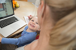 Mother and son using laptop, smiling