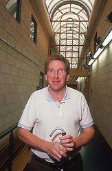 Man with visual impairment using walking stick to walk down corridor,