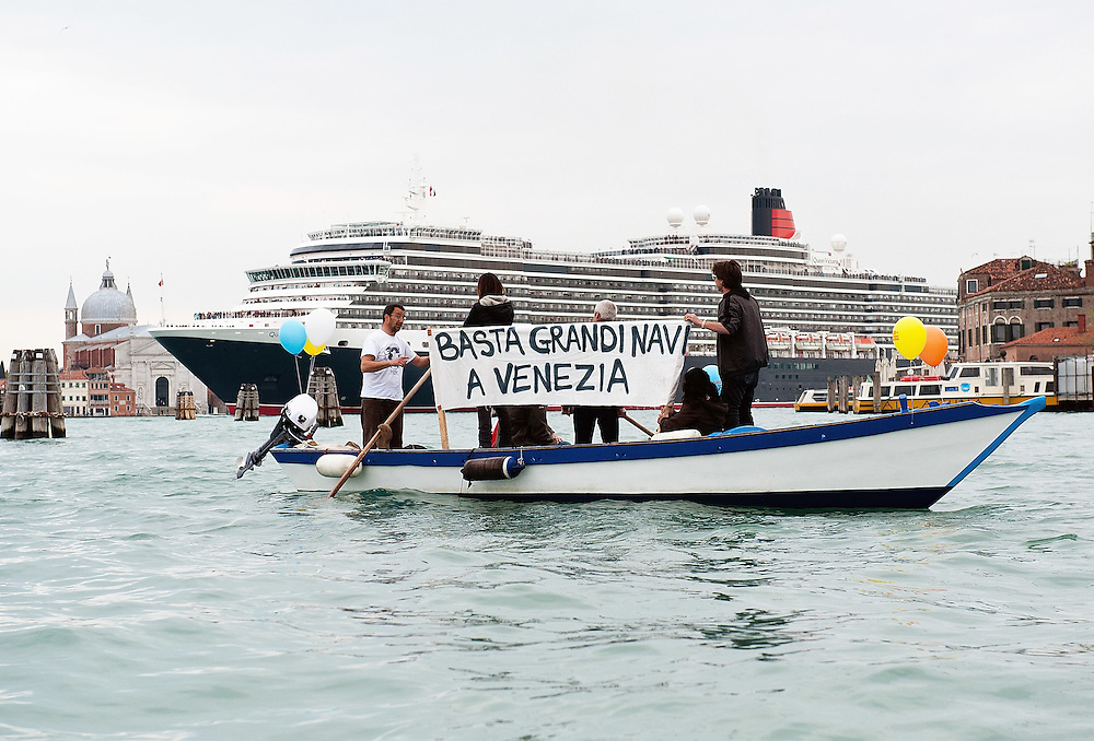 Protesters on small boats display banners against Cruise Ships crossing Venice get as close as they can to the Queen Victoria Cruise Ship in St Mark's Basin (Marco Secchi/XianPix)