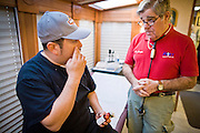 08 DECEMBER 2010 - PHOENIX, AZ: EFREN ANISTACIO (left) talks to Dr. CHARLES LEVISON, a volunteer at a Mission of Mercy mobile clinic in Phoenix, AZ, Wednesday, Dec. 8. Mission of Mercy has been providing free medical help for people in the Phoenix area since 1997. In the last two years, as the Arizona economy continued its recessionary slide, patient load at the clinics has more than doubled. Mission of Mercy, which relies on voluntary medical help and financial donations, recently acquired another mobile clinic so they could expand their reach into suburban areas they previously had not served. Mission of Mercy has provided free medical help to more than 43,000 patients in the Phoenix area since 1997.    PHOTO BY JACK KURTZ