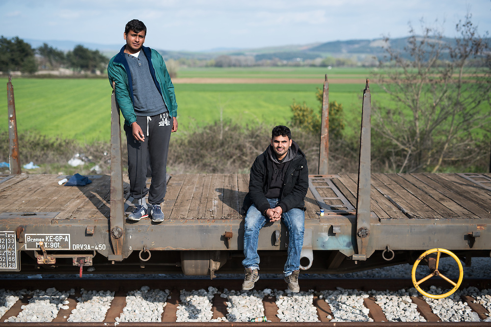 Two men from Pakistan waiting for the border to open on a parked cargo railway car in Idomeni railway station.  <br /> <br /> Thousands of refugees are stranded in Idomeni unable to cross the border. The facilities are stretched to the limit and the conditions are appalling.